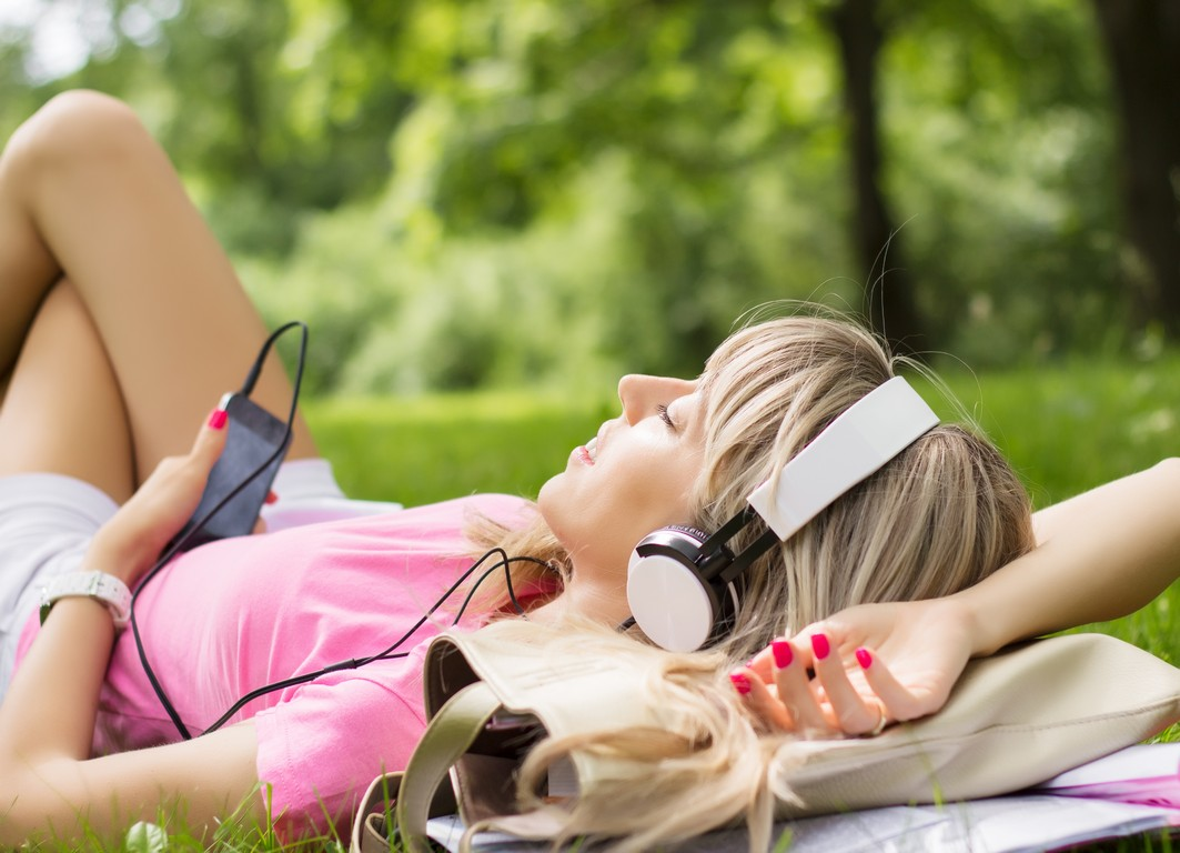 Beautiful girl enjoying music in park